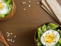 La salade des feuilles et des oeufs de laitue dans des cuvettes en bois sème le fond d'obscurité de pains de cumin Images stock