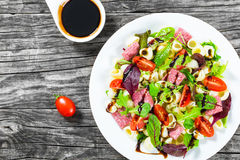 La salade délicieuse de pâtes de Shell avec les feuilles mélangées de laitue, le salami sur le plat blanc avec des écrous, le mie Images stock