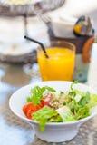 La salade fraîche dans une cuvette a servi avec le jus d'orange photos libres de droits