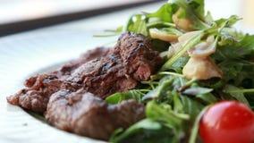La salade juteuse fraîche avec du boeuf de ruccola et des tomates-cerises a servi à un dîner romantique dans le restaurant de lux banque de vidéos