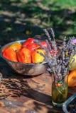 La salade rouge et jaune poivre dans la marinade pour griller et un bouquet de lavande sur la table d'été Image stock