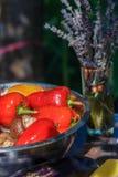 La salade rouge et jaune poivre dans la marinade pour griller et un bouquet de lavande sur la table d'été Photos libres de droits
