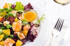 La salade saine avec les crevettes roses, la laitue, les oranges et la mangue a servi d'un plat avec de la sauce à moutarde orang Photographie stock libre de droits