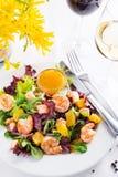 La salade saine avec les crevettes roses, la laitue, les oranges et la mangue a servi d'un plat avec de la sauce à moutarde orang Images libres de droits