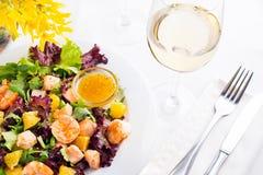 La salade saine avec les crevettes roses, la laitue, les oranges et la mangue a servi d'un plat avec de la sauce à moutarde orang Photographie stock
