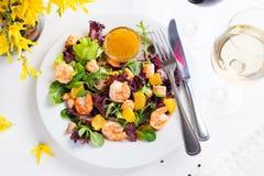 La salade saine avec les crevettes roses, la laitue, les oranges et la mangue a servi d'un plat avec de la sauce à moutarde orang Photo libre de droits