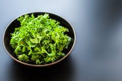 La salade verte fraîche de chou frisé part dans une cuvette sur le conseil noir avec la copie Photographie stock
