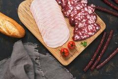 La salchicha cortó en una tabla de cortar con los tomates y el pan fresco Foto de archivo