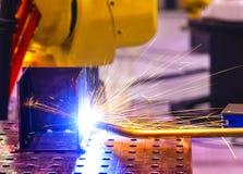 La saldatrice automatica produce la saldatura del serbatoio metallico primo piano delle fiamme blu e gialle con spruzzo La profon immagine stock libera da diritti