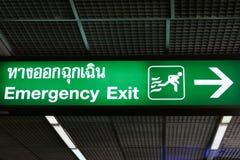 La salida de emergencia firma adentro lengua inglesa y tailandesa Fotografía de archivo
