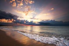 La salida del sol colorida de la playa del océano con el cielo azul y el sol profundos irradia Imagen de archivo