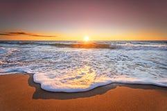 La salida del sol con el cielo azul y el sol profundos irradia Imagen de archivo libre de regalías