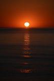 La salida del sol del mar, con el cielo centrado, rojo del sol y la reflexión larga en la superficie del agua Fotos de archivo libres de regalías