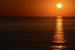La salida del sol del mar, con el sol en el cielo derecho, anaranjado y la reflexión larga en la superficie del agua Foto de archivo libre de regalías