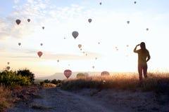 La salida del sol en las montañas con muchos globos calientes del aire en el cielo imágenes de archivo libres de regalías