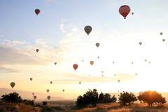 La salida del sol en las montañas con muchos globos calientes del aire en el cielo Fotos de archivo