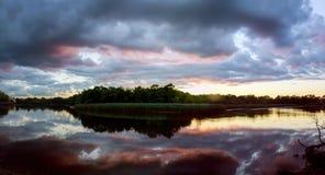 La salida del sol hermosa con las nubes brillantes reflejó en agua Foto de archivo libre de regalías