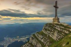 La salida del sol hermosa en las montañas y los héroes de Caraiman cruzan el monumento en las montañas de Bucegi, Cárpatos, Rumani Foto de archivo libre de regalías