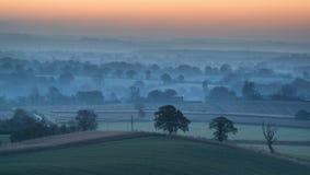 La salida del sol imponente sobre la niebla acoda en paisaje del campo Fotografía de archivo