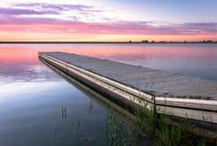 La salida del sol o la puesta del sol en un muelle de la pesca con las nubes coloridas refleja Imágenes de archivo libres de regalías