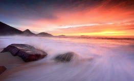 La salida del sol del océano como ondas grandes se lava sobre la playa Imagenes de archivo