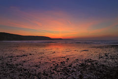 La salida del sol reflejó en la arena y los guijarros mojados de la playa del este de agua dulce Foto de archivo