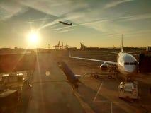 La salida del sol teñida en el aeropuerto con saca en el brillo fotos de archivo