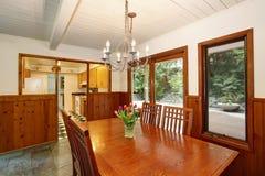 La salle à manger blanche et brune avec les fleurs fraîches sur la table mise et des murs avec la planche en bois équilibrent image stock