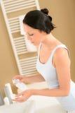 La salle de bains de jeune femme appliquent la dépose de renivellement de visage image stock