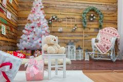 La salle est décorée des branches de pin et de l'arbre de Noël Un ours de nounours se repose sur une chaise au milieu de la salle images libres de droits