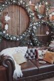 La salle est décorée pendant la nouvelle année Guirlandes de Noël, couverture blanche et oreillers sur le divan images libres de droits