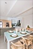 La salle à manger moderne a installé avec des bougies clignotant devant la cuisine Image libre de droits