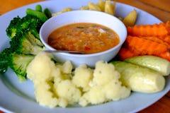 La salsa di peperoncino rosso in piccola tazza e vari tipi di verdure Fotografie Stock
