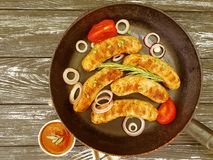 la salsiccia arrostita casalinga su una padella, il pomodoro, cipolla, arrostisce col barbecue rustico su un vecchio fondo di leg Fotografie Stock