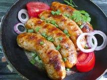 la salsiccia arrostita su una padella, il pomodoro, cipolla, arrostisce col barbecue rustico su un vecchio fondo di legno nero Fotografia Stock