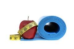 La salud de la aptitud se opone la manzana con la estera de la yoga Imágenes de archivo libres de regalías