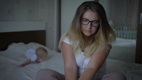La salud mental, mujer trastornada preocupante en lentes se sienta en cama en fondo del bebé de arrastre en casa almacen de video