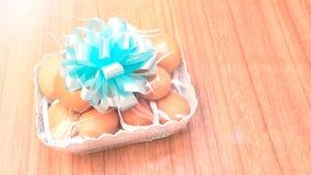 La salute del regalo è merce nel carrello che delle uova del pollo il retro colore ha spazio della copia Fotografia Stock