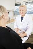 La sangre de Collecting Senior Patient sonriente del médico para la prueba adentro imágenes de archivo libres de regalías