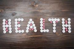 La santé de mot est présentée dans de grands comprimés roses blancs et petits Image stock