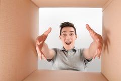 La satisfaction est une estimation Boîte étonnée d'ouverture de garçon et regard intérieur Le paquet, la livraison, surprise, cad photos stock