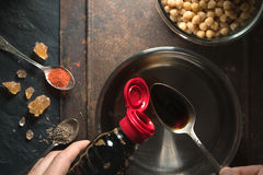 La sauce de soja est versée dans une cuillère au-dessus de la casserole Photos stock