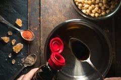 La sauce de soja est versée dans une cuillère au-dessus d'un plan rapproché de sautekeeper Image libre de droits