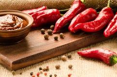 La sauce, les épices et le poivre rouges sur une cuisine embarquent Photographie stock