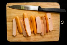 La saucisse a découpé et a servi en tranches sur un hachoir en bois léger image stock