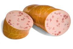 La saucisse de bâton avec des morceaux de viande a coupé en 2 moitiés Photographie stock libre de droits