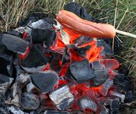 La saucisse est faite frire sur le feu Photo stock