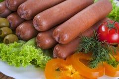La saucisse fumée avec les tomates et la laitue part sur un plat photo libre de droits