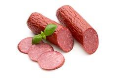 La saucisse fumée de salami, basilic part sur le coupe-circuit blanc de fond Photo stock