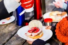 La saucisse rôtie avec le ketchup a servi dehors à la table de pique-nique Photographie stock